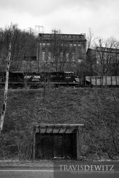 A Norfolk Southern coal train passes between an abandoned bus stop and power plant at Maybeury, West Virginia.
