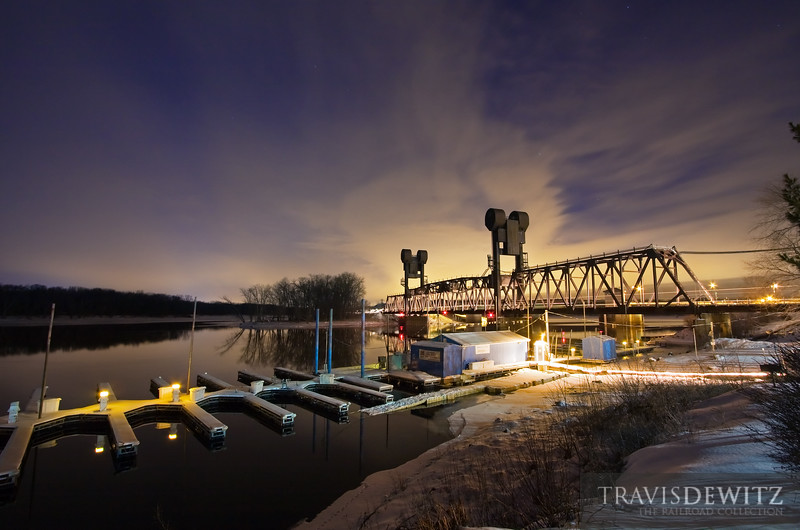 """A BNSF train glides over the Prescott lift bridge over an empty boat dock on an almost eerily calm St. Croix River with a mirror like surface.  Travis Dewitz <a href=""""http://www.therailroadcollection.com/latest-works/"""" target=""""_blank"""">The Railroad Collection</a>"""