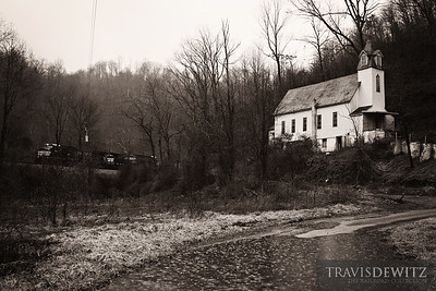 One of many Norfolk Southern coal trains work up grade towards Bluefield, West Virginia past this old church sitting in the rain in Switchback.  Travis Dewitz The Railroad Collection