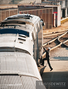 A worker on the ground climbs up to talk to the engineer before servicing the train at Amtrak's Lumber Street Yard in Chicago.  Travis Dewitz The Railroad Collection