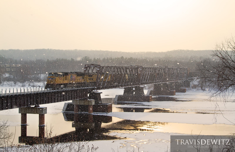 "A Union Pacific frac sand train slowly crosses the Chippewa River in Chippewa Fall, Wisconsin. The train is headed to Norma to be transfered to the Wisconsin Northern for loading in New Auburn, Wisconsin. The section of the bridge that the train has just started crossing was replaced after a fire destroyed the old trestle.  Travis Dewitz <a href=""http://www.therailroadcollection.com/latest-works/"" target=""_blank"">The Railroad Collection</a>"