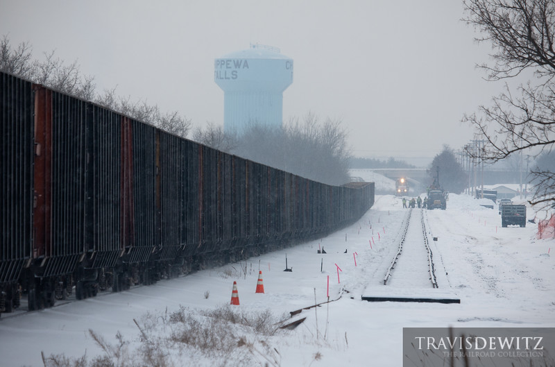 """Empty hoppers fly through the snow headed to New Auburn, Wisconsin to get loaded with frac sand which is used for drilling operations. A Wisconsin Northern GP15 idles on the spur track as crews are in the process of building the new lead for the EOG Resources, Inc. sand loading facility yard.  Travis Dewitz <a href=""""http://www.therailroadcollection.com/latest-works/"""" target=""""_blank"""">The Railroad Collection</a>"""