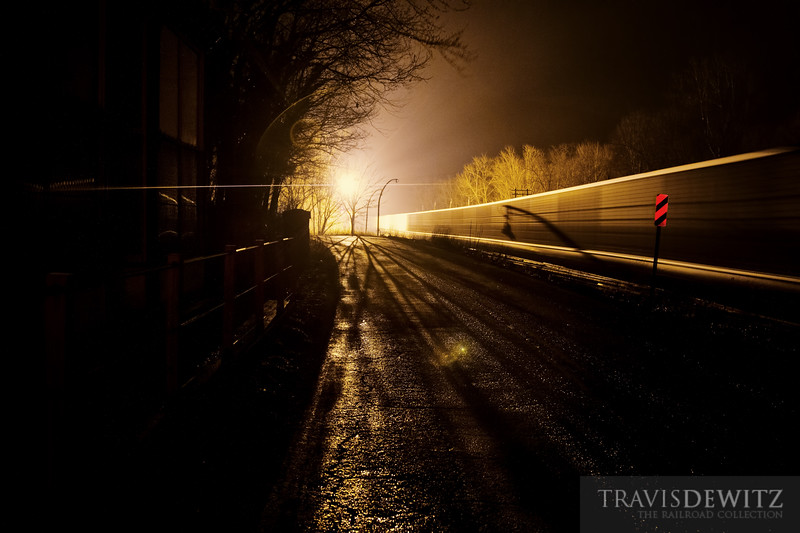 """A shadow of the unique light fixtures around Prince, West Virginia can be seen against the glass like finish of the aluminum CSX coal hoppers traveling along State Road 41.  Travis Dewitz <a href=""""http://www.therailroadcollection.com/latest-works/"""" target=""""_blank"""">The Railroad Collection</a>"""