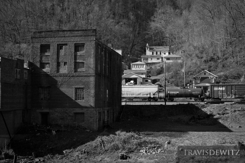 Looking across the river at the backside of downtown Iaeger, West Virginia as a train passes through. A great view to see how the town in this area grow up into any space that they can with the church being built at the top.