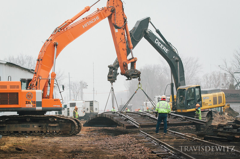 Construction crews use excavators to lift a prefab switch into place in Cameron, Wisconsin. Canadian National has taken control back from Wisconsin Northern when the frac sand plant opened up on the line.