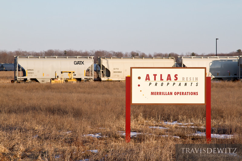 Sand hoppers and a trac mobile sit behind the Atlas Resin Proppants sign for their Merrillan, WI operations.