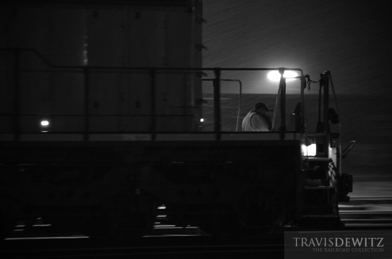 """The conductor toughs out the weather guiding back the head end power back onto the rest of their train in Altoona, WI.  Travis Dewitz <a href=""""http://www.therailroadcollection.com/latest-works/"""" target=""""_blank"""">The Railroad Collection</a>"""