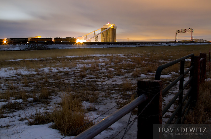 "A BNSF coal train waits it's turn as the signal bridge glows all reds at Codero Mine.  Travis Dewitz <a href=""http://www.therailroadcollection.com/latest-works/"" target=""_blank"">The Railroad Collection</a>"