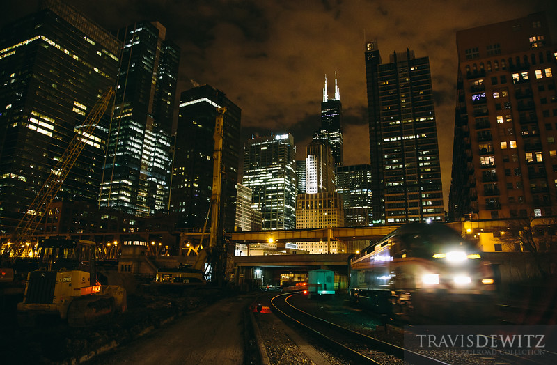 An out bound Metra passenger train heads north out of Chicago Union Station. Construction equipment can be seen on the right preparing the ground for a new apartment building.