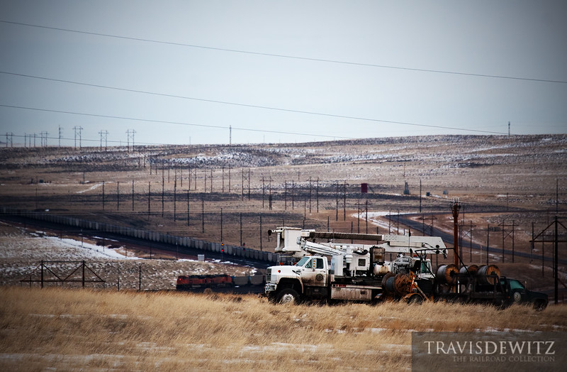 """A couple of utility trucks are part of an Wyoming lanscape of power poles and power lines. Another coal train with BNSF DPUs head back to a coal loadout in the Powder River Basin to load up with coal which in turn will be used to generate more electricty which will use an infrastructure similiar to what can be seen here.  Travis Dewitz <a href=""""http://www.therailroadcollection.com/latest-works/"""" target=""""_blank"""">The Railroad Collection</a>"""