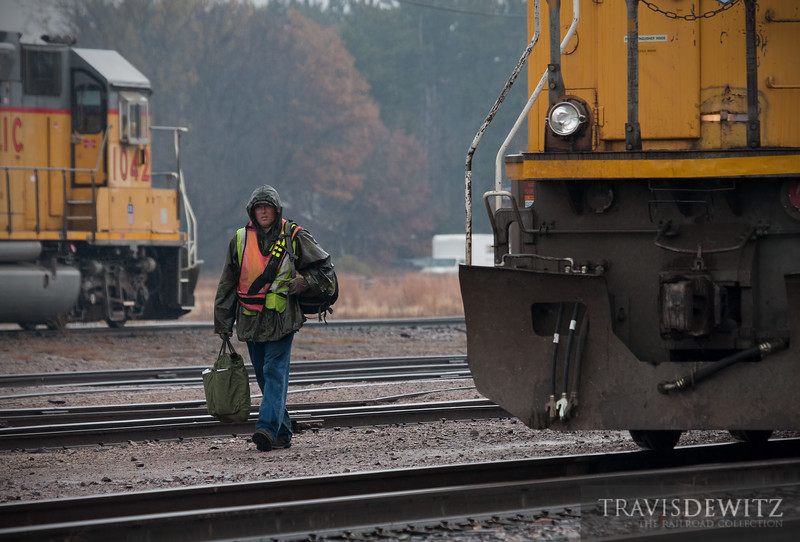 """With grip in hand, a crew member ends his shift on this dreary October day in Altoona, Wisconsin.  Travis Dewitz <a href=""""http://www.therailroadcollection.com/latest-works/"""" target=""""_blank"""">The Railroad Collection</a>"""
