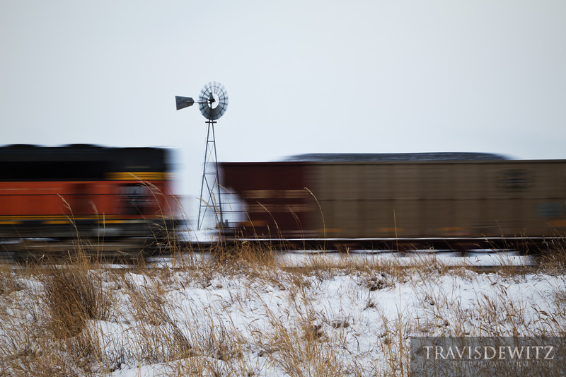 """The Aermotor windmill is working hard as a stiff cold wind blows across the Wyoming plains. A BNSF coal train heads straight into the gusty wind making it's way north towards Gillette.  Travis Dewitz <a href=""""http://www.therailroadcollection.com/latest-works/"""" target=""""_blank"""">The Railroad Collection</a>"""