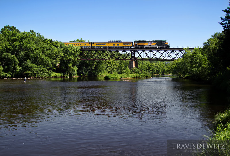 """Union Pacific CNW heritage unit number 1995 leads the 1st trip of the Operation Lifesaver train across the Eau Claire River trestle and back to Altoona, Wisconsin to prepare for the 2nd trip. A fly fisherman looks on as the train crosses overhead.  Travis Dewitz <a href=""""http://www.therailroadcollection.com/latest-works/"""" target=""""_blank"""">The Railroad Collection</a>"""