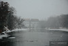 A westbound Union Pacific train crosses the Eau Claire River high above the waterfowl below in a very heavy snowfall.