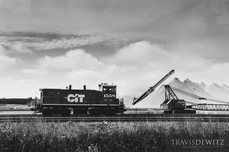 A CIT switcher sits outside a frac sand plant near New Auburn, Wisconsin as piles of sand rise towards the sky in the background.