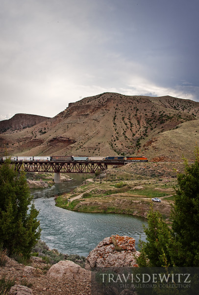 "A BNSF manifest works up the Wind River on the edge of a storm on their way towards Thermopolis, Wyoming.  Travis Dewitz <a href=""http://www.therailroadcollection.com/latest-works/"" target=""_blank"">The Railroad Collection</a>"