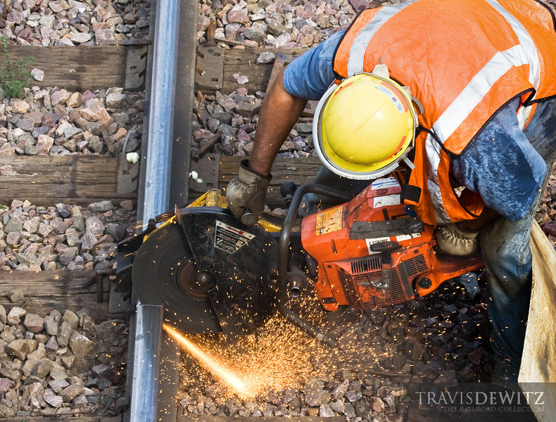 """A Union Pacific MOW worker cuts a piece of stick rail just outside the Altoona yard so that the new welded rail can be spliced in for the night before work resumes again the next day.  Travis Dewitz <a href=""""http://www.therailroadcollection.com/latest-works/"""" target=""""_blank"""">The Railroad Collection</a>"""