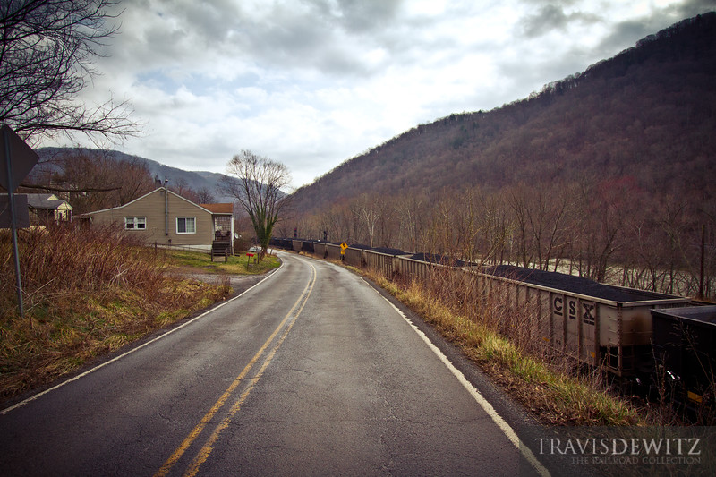 A CSX coal train sails towards Prince, West Virginia between the narrow road and the New River.