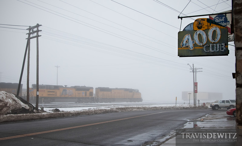 """A thick morning fog hang over Altoona, Wisconsin as a Union Pacific freight lumbers east past the """"400"""" Club.  Travis Dewitz <a href=""""http://www.therailroadcollection.com/latest-works/"""" target=""""_blank"""">The Railroad Collection</a>"""