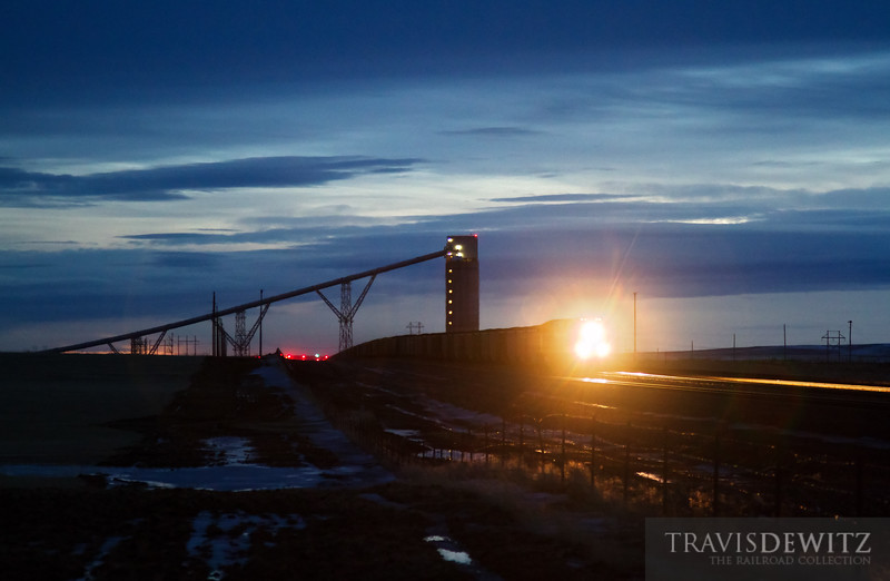 """The very last of the days light illuminates the skies over the Black Thunder West coal loadout near Reno Junction. A loaded BNSF unit coal train lights it's way north up the Orin Subdivision.  Travis Dewitz <a href=""""http://www.therailroadcollection.com/latest-works/"""" target=""""_blank"""">The Railroad Collection</a>"""