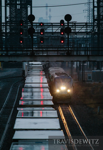 An Amtrak passenger train speeds past a Norfolk Southern trailer train through the Arcelor Mittal steel complex in East Chicago, Indiana.