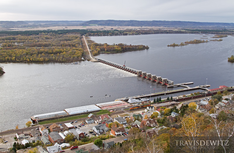 """A lot of action going on in the small town of Alma, Wisconsin, which sits between a bluff and the Mississippi River. A barge can be seen exiting from the lock below as a BNSF ore train flies down the river. Fishermen can be seen fishing below the dam as the city streets are full of activity. A beautiful scene.  Travis Dewitz <a href=""""http://www.therailroadcollection.com/latest-works/"""" target=""""_blank"""">The Railroad Collection</a>"""