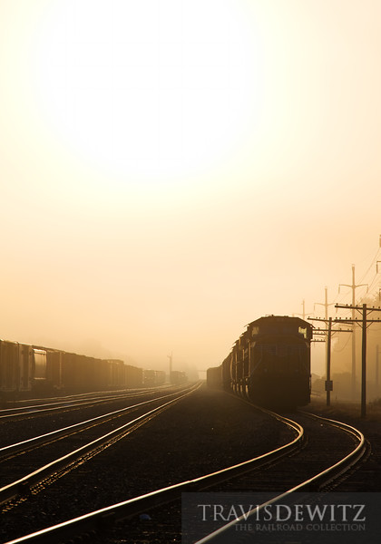 """The rising sun burns off the early morning fog over the Union Pacific's Altoona, Wisconsin yard which still has some code line poles still standing along side it.  Travis Dewitz <a href=""""http://www.therailroadcollection.com/latest-works/"""" target=""""_blank"""">The Railroad Collection</a>"""