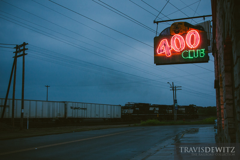 A Norfolk Southern Road Railer sails east through Altoona, Wisconsin past the 400 Club's lit neon sign on a rainy evening.
