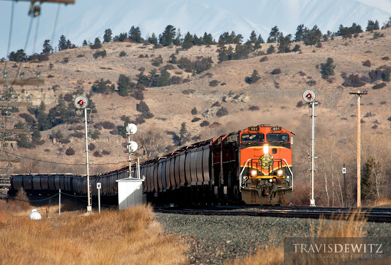 Eastbound BNSF 991 powers into the sun splitting the signals neat Greycliff, Montana under the looming Crazy mountains.