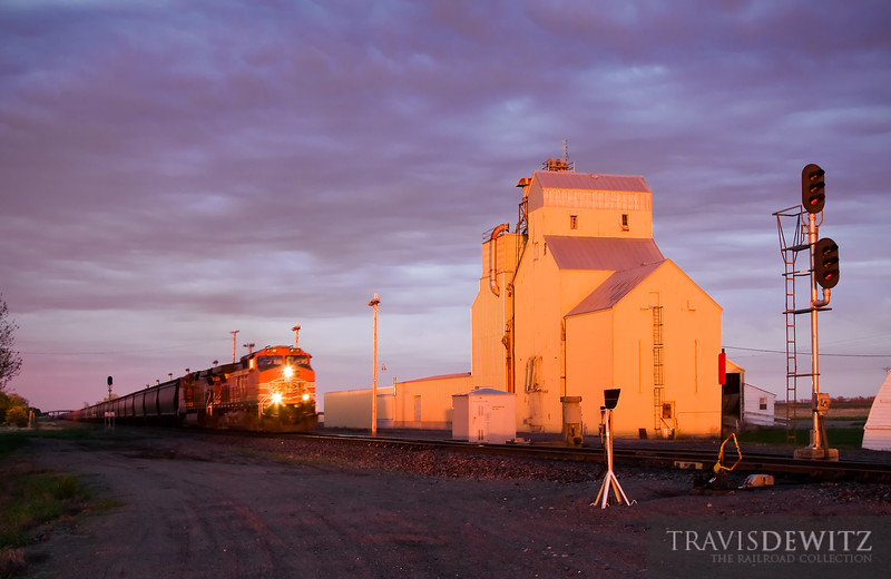 """A BNSF worm train rushes west through South Berea, North Dakota on the Jamestown Subdivision as the last of the sun colors a grain elevator with a warm glow.  Travis Dewitz <a href=""""http://www.therailroadcollection.com/latest-works/"""" target=""""_blank"""">The Railroad Collection</a>"""