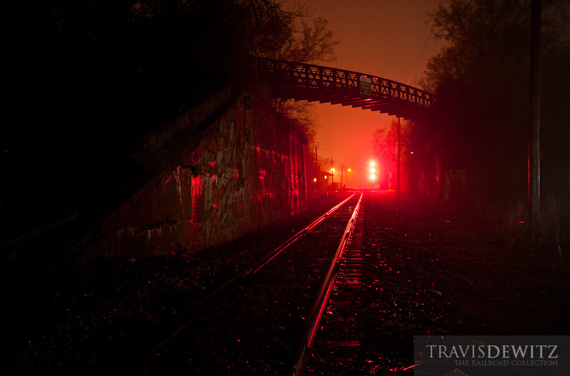 """Red signal lights protect the crossing at Rondout as it rains through the night.  Travis Dewitz <a href=""""http://www.therailroadcollection.com/latest-works/"""" target=""""_blank"""">The Railroad Collection</a>"""