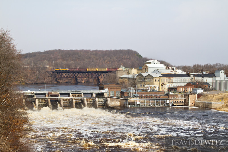 """The Menards local job pushes it's train across the Chippewa River back to Altoona yard. The Dells Dam can be seen in the foreground holding back near flood stage waters of the Chippewa River. This is one of Xcel Energy's hydro dams that was recently upgraded in 2009. The original dam at this location was all wood and was used to create a holding pond, named Dells Pond, for the local logging saw mills in the area. Now Cascades Tissue's paper mill is on that site.  Travis Dewitz <a href=""""http://www.therailroadcollection.com/latest-works/"""" target=""""_blank"""">The Railroad Collection</a>"""