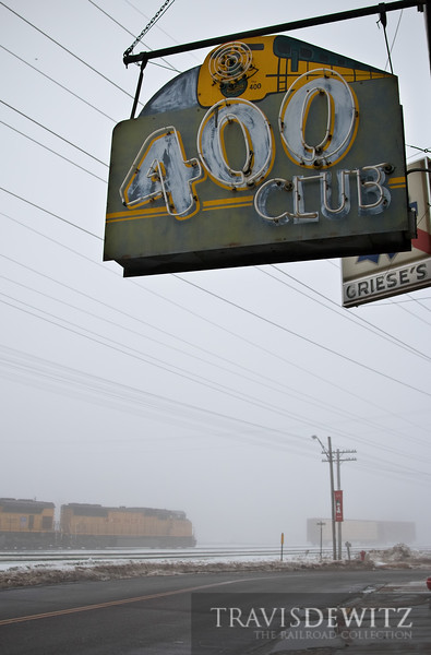 """The 400 Club sign hangs over a Union Pacific freight as it lumbers east through a thick morning fog in Altoona, Wisconsin.  Travis Dewitz <a href=""""http://www.therailroadcollection.com/latest-works/"""" target=""""_blank"""">The Railroad Collection</a>"""