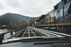 An empty coal train crosses a rail/road shared bridge ove the New River as it leaves Thurmond headed to Pax, West Virginia.