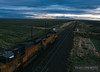 Two Union Pacific SD9043MAC series locomotives sail down grade towards Rawlins, Wyoming.
