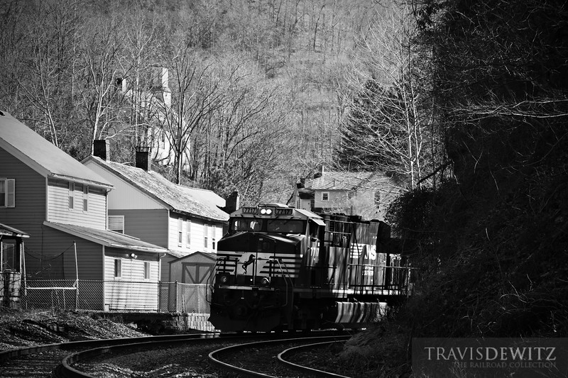 """Norfolk Southern 7717 pulls a string of coal cars through the town of Gary, West Virginia on their way towards Welch. The local church can be seen on the hillside towering over the town below.  Travis Dewitz <a href=""""http://www.therailroadcollection.com/latest-works/"""" target=""""_blank"""">The Railroad Collection</a>"""