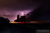 A supercell thunderstorm rages on across the Texas night sky as the flashes of lightning silhouette tall cement grain silos as a BNSF container train flashes east through Umbarger at milepost 581.