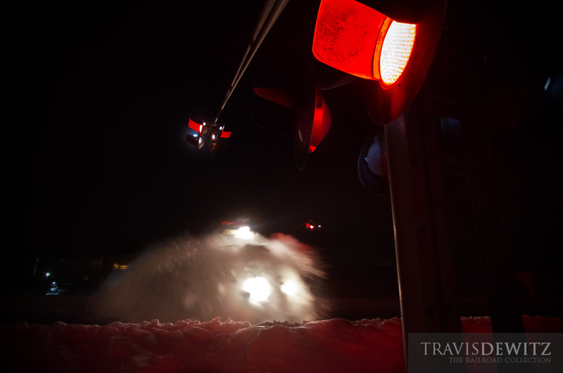 """The Union Pacific local job headed up the Chippewa Falls Sub a couple days after a blizzard dropped 21 inches of snow on the area. LLPX 2205 moves along as it busts through snow banks Chippewa Falls as the red crossing lights flash back and forth.  Travis Dewitz <a href=""""http://www.therailroadcollection.com/latest-works/"""" target=""""_blank"""">The Railroad Collection</a>"""