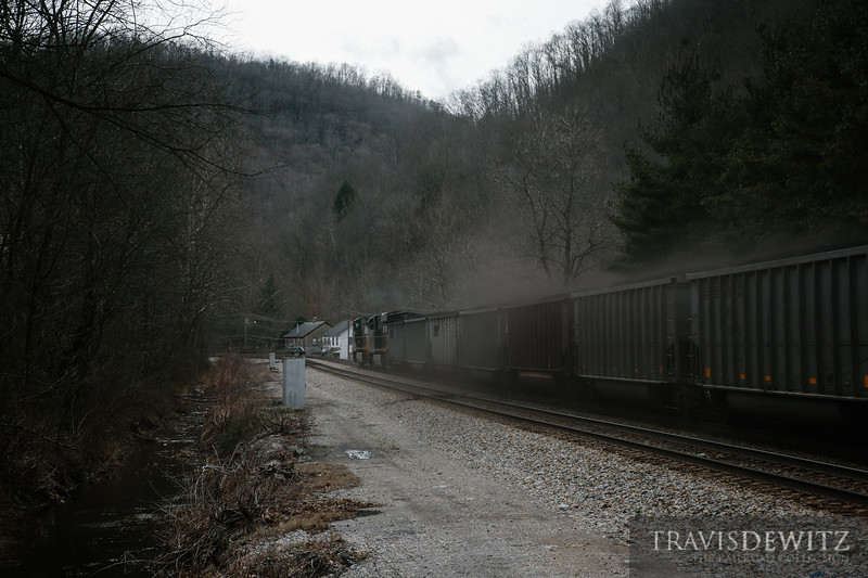 Coal dust blows off the top of loaded Norfolk Southern Top Gon coal hoppers as they pick up speed through Maitland, West Virginia.