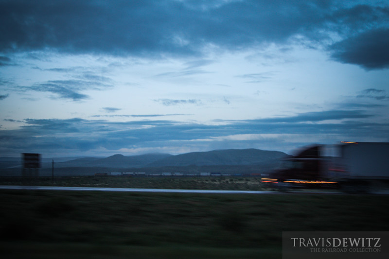 A Union Pacific container train flies west as a semi truck on Interstate 80 heads east towards Rawlins, Wyoming.