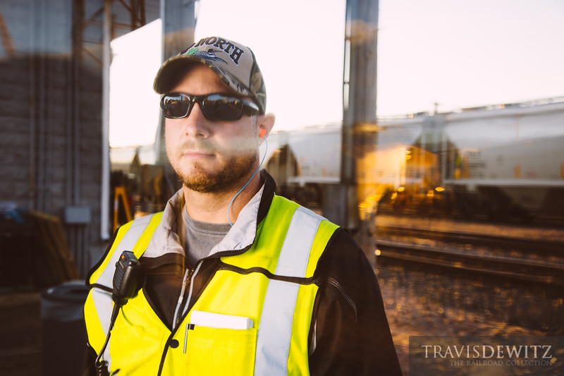 Portrait of an Union Pacific conductor photographed through antique glass with a reflection of a locomotive.