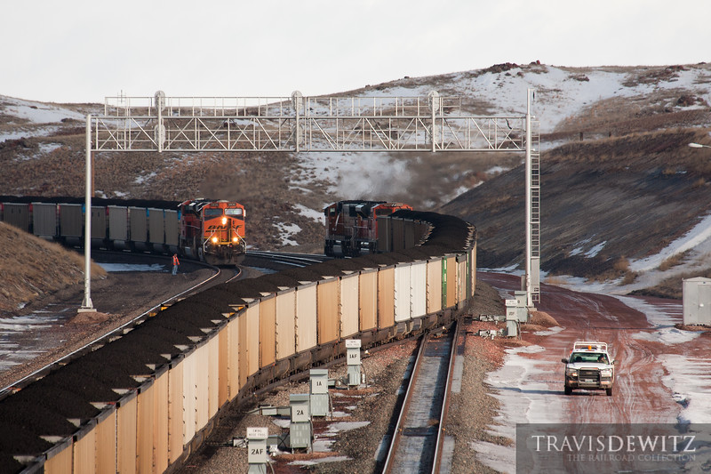 Two loaded BNSF coal trains meet south of Donkey Creek Jct. as a MOW worker inspects the switch heaters along the line.