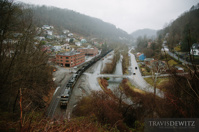 An empty Norfolk Southern coal train rolls west through Welch, West Virginia about to enter the tunnel portal on a foggy March morning. From this vantage point you can see how all the homes cling to the steep mountain sides. The creek and road weave around the mountains as the tracks borrow through here.