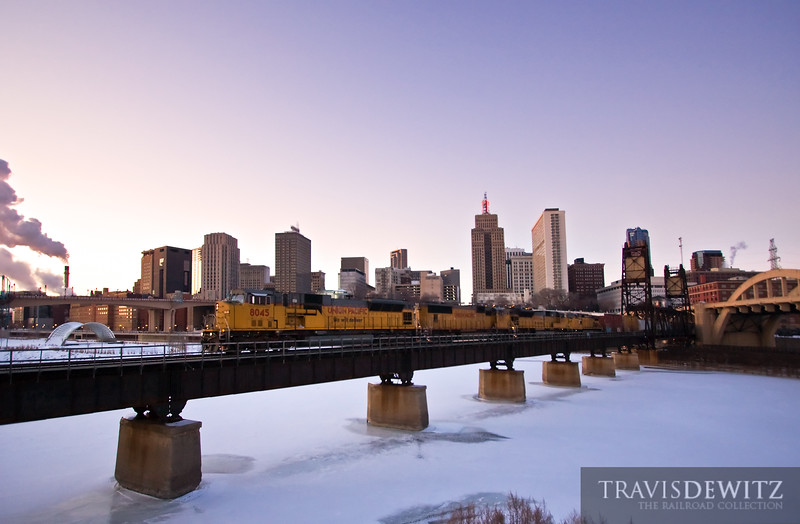 "Four Union Pacific locomotives pull their train across the Robert Street lift bridge as the setting sun paints the sky in gorgeous shades of color on a bitterly cold below zero day.  Travis Dewitz <a href=""http://www.therailroadcollection.com/latest-works/"" target=""_blank"">The Railroad Collection</a>"