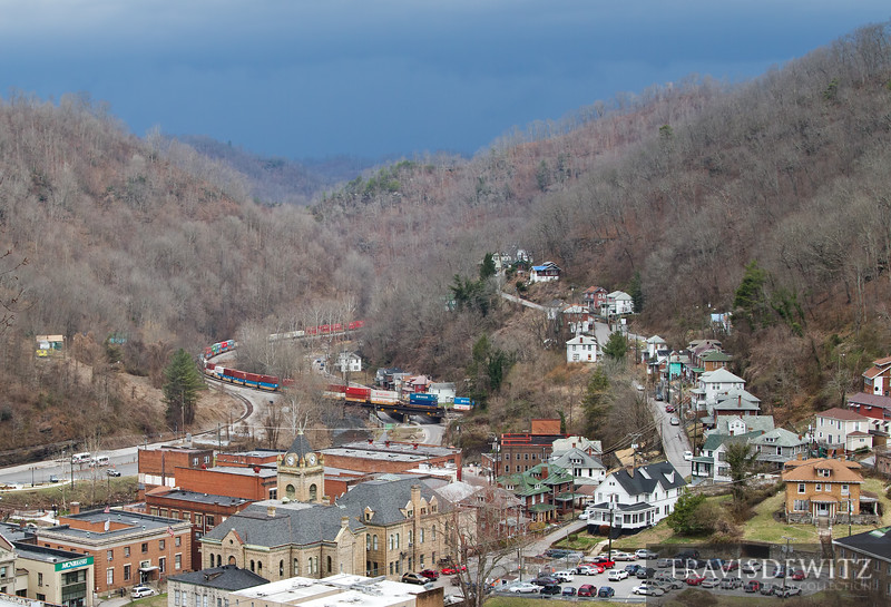 """The graceful arc of brightly colored containers swing out of the mountain and through the town of Welch, West Virginia. A severe spring storm is quickly moving across the area as well. Jeannette Walls, the author of The Glass Castle, lived in one of the homes on the right.  Travis Dewitz <a href=""""http://www.therailroadcollection.com/latest-works/"""" target=""""_blank"""">The Railroad Collection</a>"""