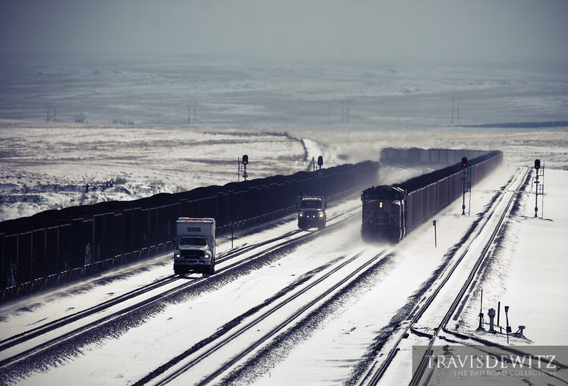 """Herzog MOW trucks inspect the tracks on Logan Hill as two fully loaded trains glide down hill towards Bill, Wyoming on a cold January winter day.  Travis Dewitz <a href=""""http://www.therailroadcollection.com/latest-works/"""" target=""""_blank"""">The Railroad Collection</a>"""