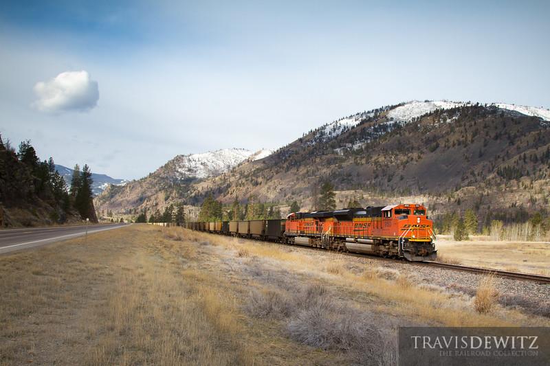A BNSF Railway coal train travels east through Perma, Montana with a beautiful mountain backdrop.