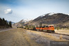 A BNSF Railway coal train travels east through Perma, Montana with a beautiful mountain backdrop.