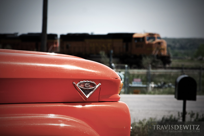 """A classic orange Chevrolet truck stands guard of this dirt drive just outside Laurel, Montana while a BNSF freight sits and waits along the road for the Montana Rail Link's dispatcher to give them some trackage.  Travis Dewitz <a href=""""http://www.therailroadcollection.com/latest-works/"""" target=""""_blank"""">The Railroad Collection</a>"""