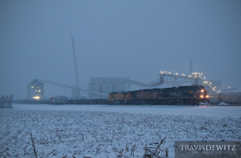 """The first snow of the year paints the night white as Wisconsin Northern employees move the Union Pacific power around for the first Cameron, Wisconsin frac sand train. UP 6177 will be the only unit to pull the empty sand train to Cameron while the two other units will remain in Norma. The two WN GP15s will hitch a ride on the rear of the empty train. This train will come back loaded a couple of days later with UP 6177 as a DPU and the other two units as the leaders. The new EOG Resources, Inc. plant makes a great back drop on this cold night.  Travis Dewitz <a href=""""http://www.therailroadcollection.com/latest-works/"""" target=""""_blank"""">The Railroad Collection</a>"""